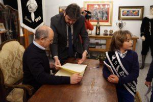 El alcalde firma en el libro de los Estudiantes