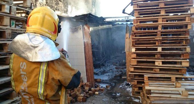 Los bomberos sofocan el fuego de varios palés agrupados en un patio de la calle La Rambla