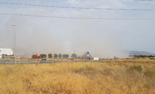 Bomberos y dos helicópteros trabajan en sofocar un incendio de matorral junto a la autovía